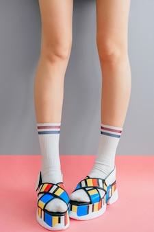 Belles jambes féminines en chaussettes blanches et chaussures colorées