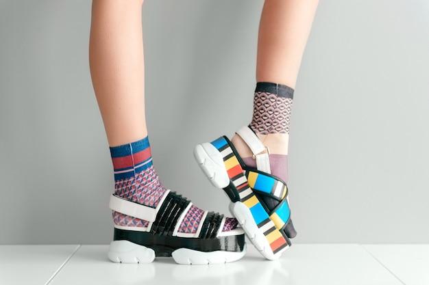 Belles jambes féminines en chaussettes et sandales dépareillées colorées