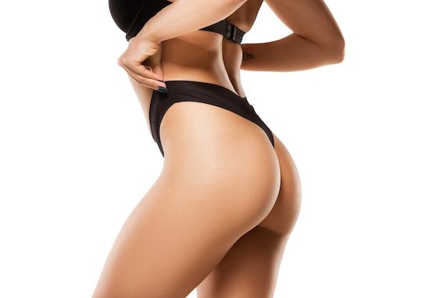 Belles jambes féminines, fesses et ventre isolés sur mur blanc.