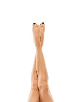Belles jambes féminines isolées sur mur blanc. beauté, cosmétiques, spa, épilation, traitement et concept de remise en forme. corps en forme et sportif, sensuel avec une peau soignée en sous-vêtements. espace de copie.