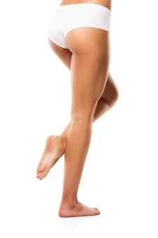 Belles jambes féminines isolées sur mur blanc