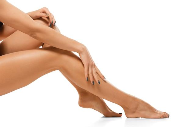 Belles jambes féminines isolées sur mur blanc.
