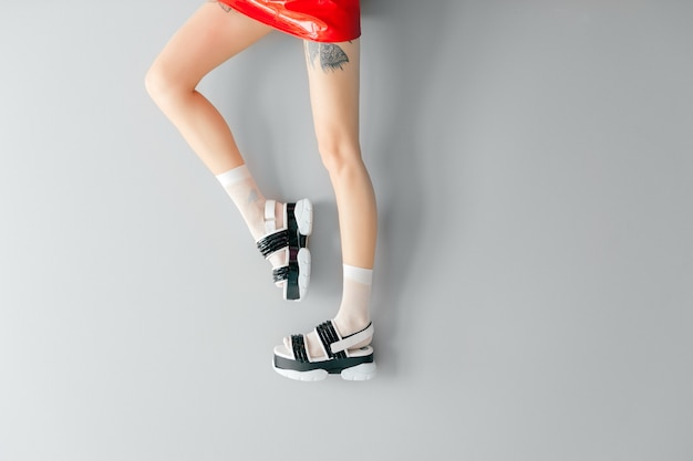 Belles jambes féminines en sandales à la mode et chaussettes blanches
