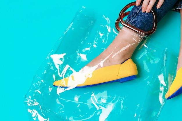 Les belles jambes féminines sont habillées de chaussures jaunes élégantes sans talon. sandales d'été jaune clair