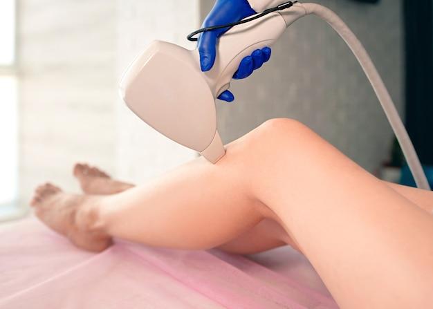 Belles jambes de femme lisses pendant l'épilation au laser