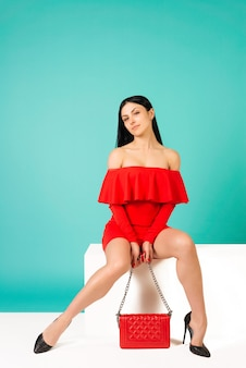 Belles jambes femme vêtue d'une robe rouge avec sac à main sac à main avec des chaussures à talons hauts assis sur le banc blanc