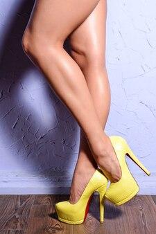 Belles jambes de femmes en chaussures à talons hauts en peau de serpent jaune