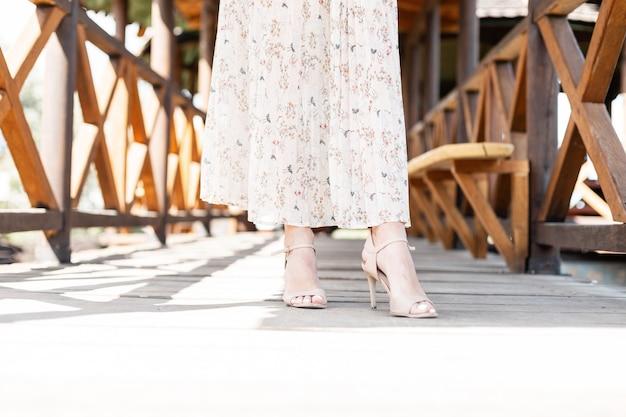 Belles jambes des femmes dans des chaussures d'été en cuir à la mode avec un talon dans une jupe à la mode sur une passerelle en bois