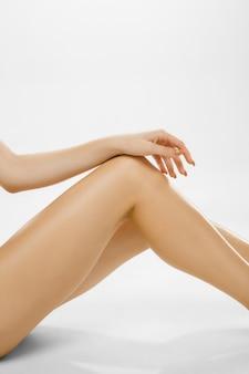 Belles jambes de femmes isolées sur blanc