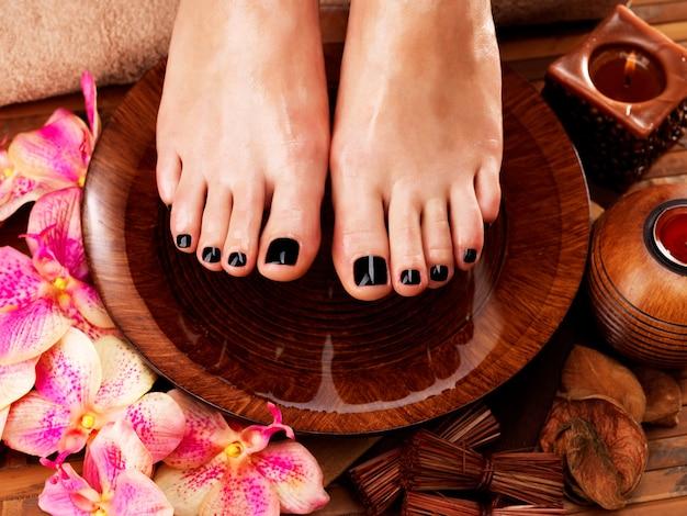 Belles jambes de femmes avec pédicure noire après les procédures de spa - concept de traitement spa