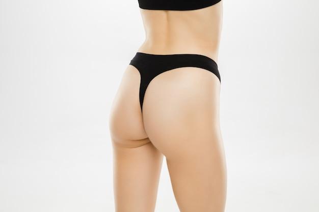 Belles jambes et hanches féminines isolées sur fond blanc. beauté, cosmétiques, spa, épilation, traitement et concept de remise en forme. corps en forme et sportif, sensuel avec une peau soignée en sous-vêtements.