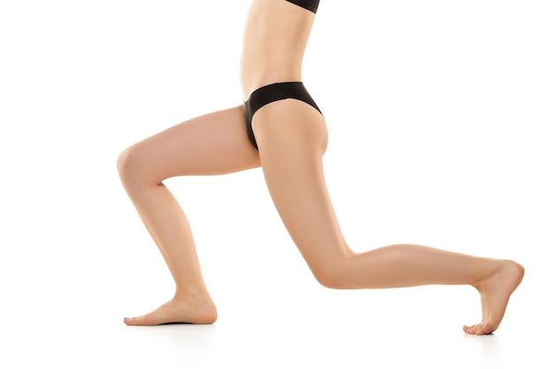 Belles jambes, hanches et ventre féminins isolés sur blanc
