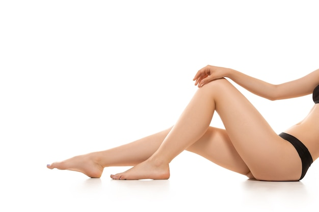 Belles jambes, hanches et ventre féminins isolés sur fond blanc, beauté