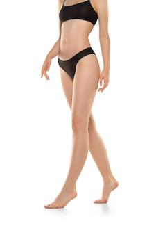 Belles jambes, hanches et ventre féminins isolés sur mur blanc, beauté
