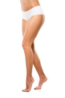 Belles jambes et ventre féminins isolés sur mur blanc