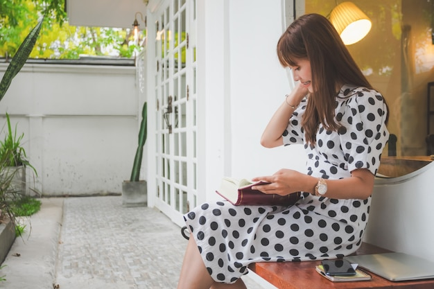 Belles jeunes asiatiques assis livre de lecture en plein air