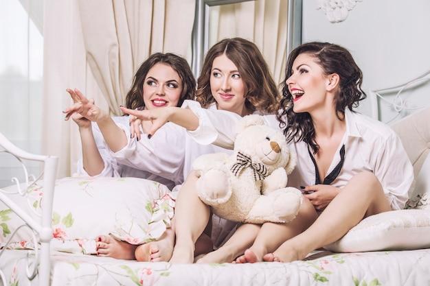 Belles jeunes femmes amis bavardant dans la chambre en chemises blanches