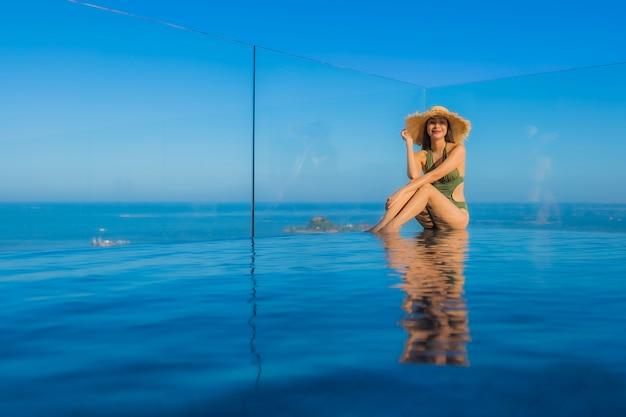 Belles jeunes femmes asiatiques sourire heureux se détendre autour de la piscine extérieure de l'hôtel pour voyager en vacances