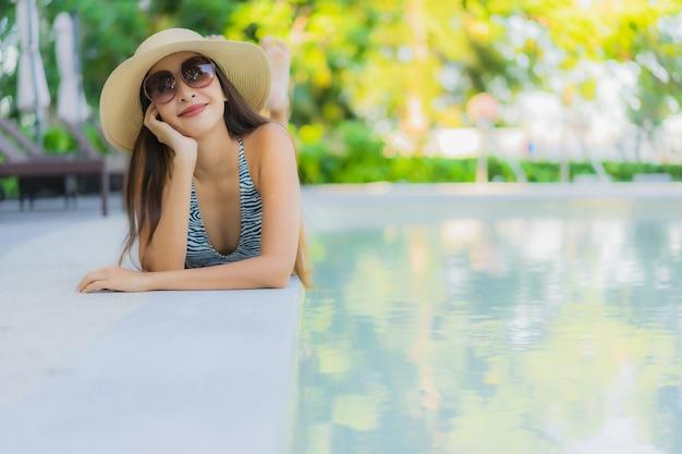 Belles jeunes femmes asiatiques sourire heureux se détendre autour de la piscine extérieure de l'hôtel resort