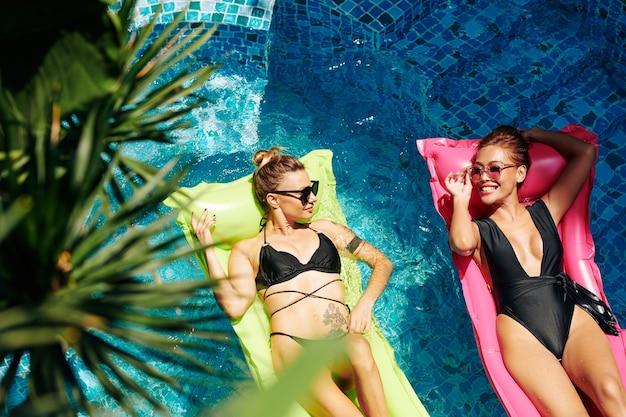 Belles jeunes femmes en bikini appréciant de passer une chaude journée d'été dans la piscine de l'hôtel et de bronzer sur des matelas flottants