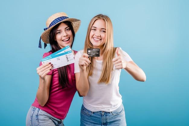 Belles jeunes femmes avec des billets d'avion et carte de crédit sur bleu