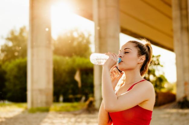 Belles jeunes femmes buvant de l'eau après avoir couru