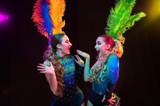 Belles jeunes femmes en carnaval, costume de mascarade élégant avec des plumes sur un mur noir à la lumière du néon