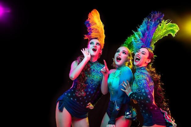 Belles jeunes femmes en carnaval, costume de mascarade élégant avec des plumes sur un mur noir en néon