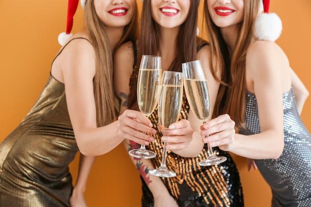 Belles jeunes femmes avec champagne célébrant noël en couleur