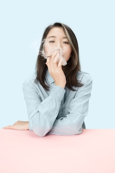 Belles jeunes femmes coréennes fumant un cigare alors qu'il était assis à table au studio.