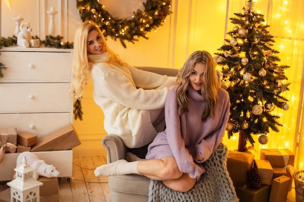 De belles jeunes femmes élégantes et heureuses en pull tricoté à la mode sont assises dans un fauteuil près d'un arbre de noël et de décorations. week-end d'hiver en famille
