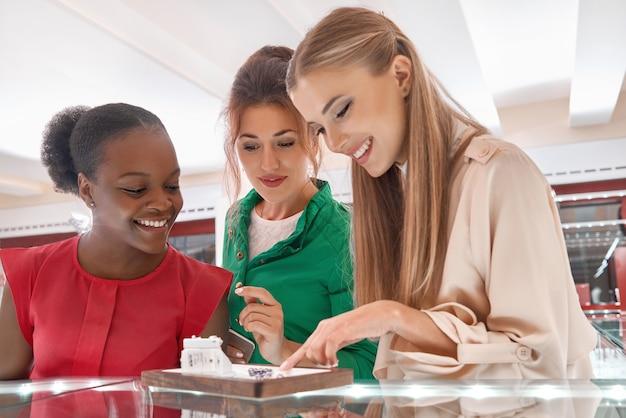 Belles jeunes femmes examinant des bijoux