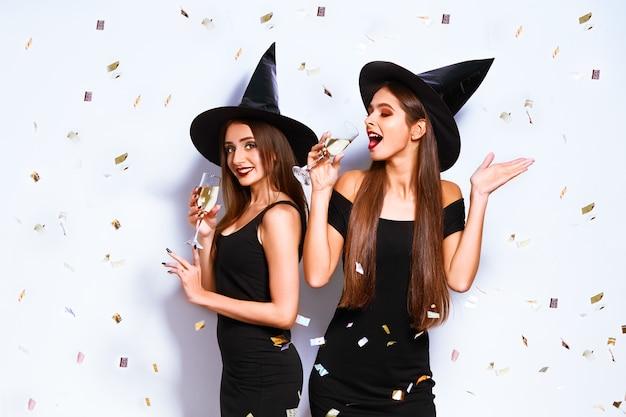 Belles jeunes femmes habillées en sorcière pour la fête d'halloween