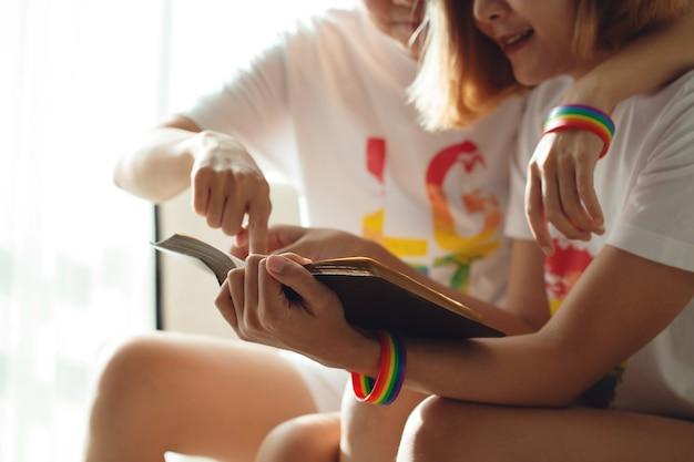 Belles jeunes femmes lesbiennes lgbt assis sur un canapé lisant un livre ensemble