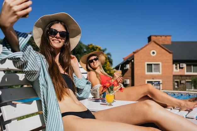 De belles jeunes femmes prennent un selfie près de la piscine.