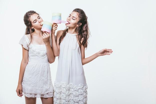 Belles jeunes femmes en robes blanches avec barbe à papa colorée dans les mains