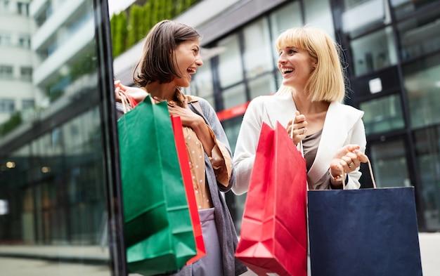 Belles jeunes femmes avec des sacs à provisions s'amusant dans la rue de la ville