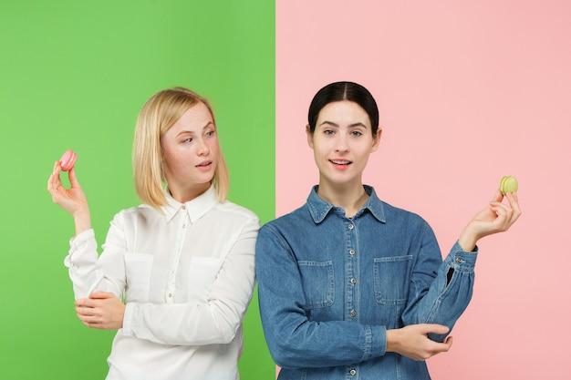 Belles jeunes femmes tenant la pâtisserie macarons dans ses mains