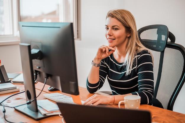 Belles jeunes femmes travaillent dur dans son bureau.