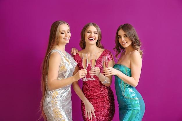 Belles jeunes femmes avec des verres de champagne sur la couleur