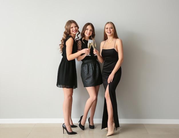 Belles jeunes femmes avec des verres de champagne près du mur clair