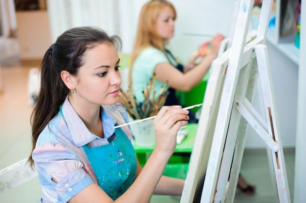 Belles jeunes filles dessine un tableau peint sur une leçon d'art