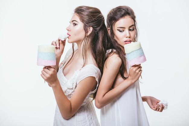 Belles jeunes filles en robes blanches avec barbe à papa colorée dans les mains