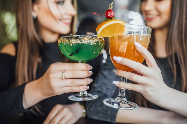 De belles jeunes filles sont assises sur la terrasse d'été d'un café moderne et boivent des cocktails rafraîchissants en orange et vert.