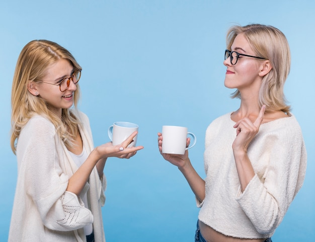 Belles jeunes filles avec des tasses à café