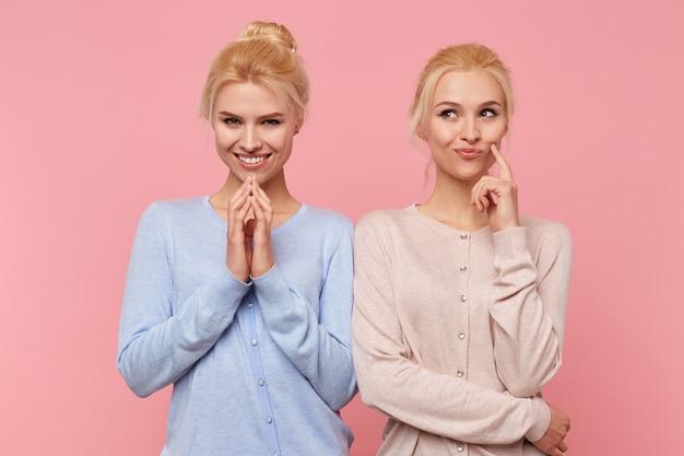 De belles jeunes jumelles blondes ont conçu quelque chose d'intéressant et ne veulent révéler leur secret à personne. regardez mystérieux et réfléchi isolé sur fond rose.