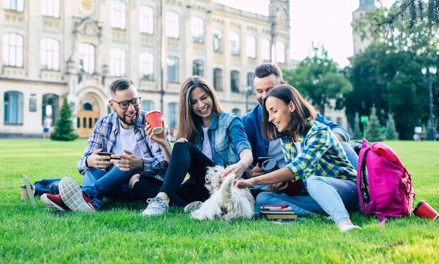 Belles jeunes meilleurs amis avec petit chien drôle sur la pelouse s'amusent et se détendent