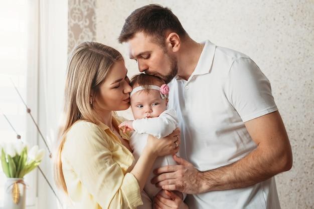 Belles jeunes parents embrassent leur petite fille dans une pièce lumineuse