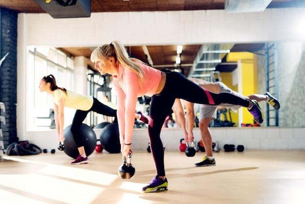 Belles jeunes sportifs travaillent avec kettlebell dans la salle de gym.