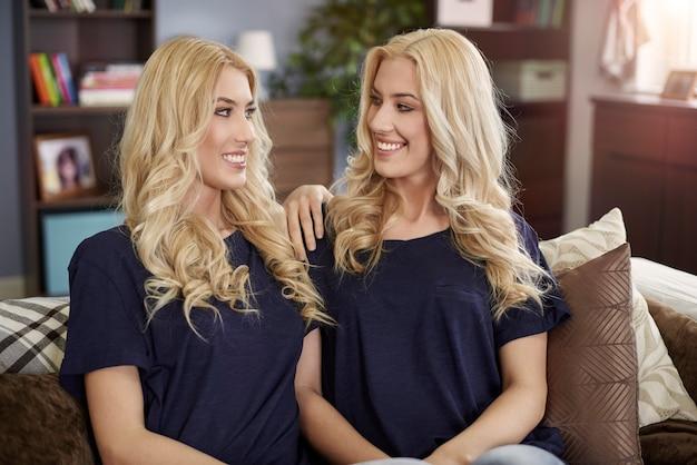 Belles jumelles blondes assis dans le salon